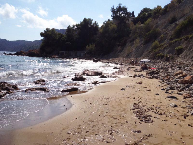 La playa presenta una orilla con arena y còdols (cantos rodados)