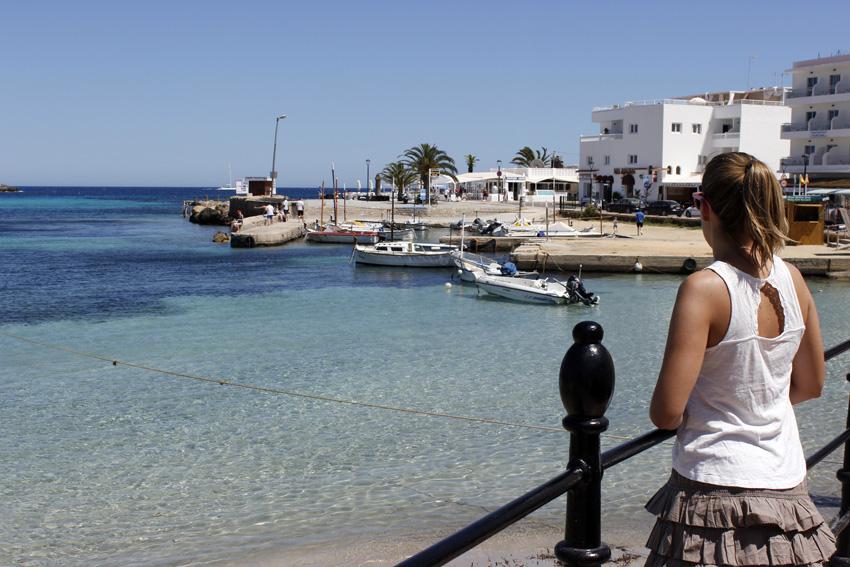 Una turista junto al pequeño puerto situado en la playa de Es Canar