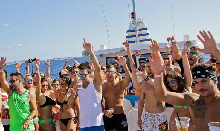 Chicos y chicas pasándoselo en grande en una fiesta en barco en Ibiza