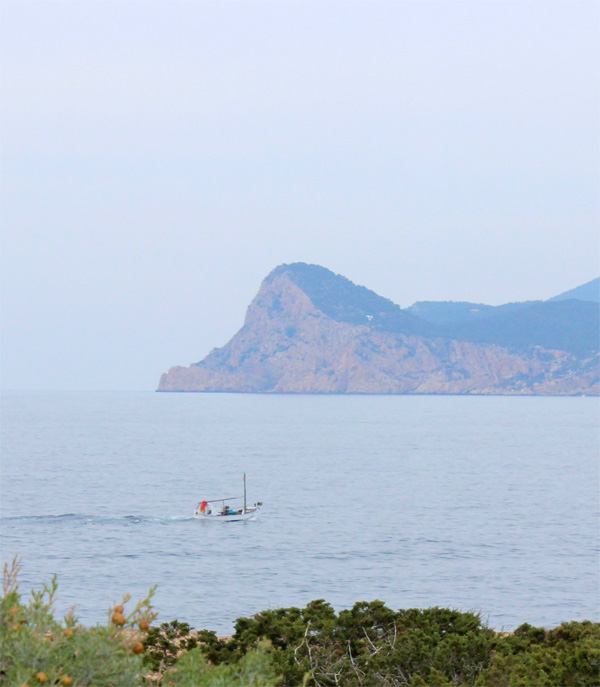Un llaüt de pesca cruza por delante de Es Cap Nonó