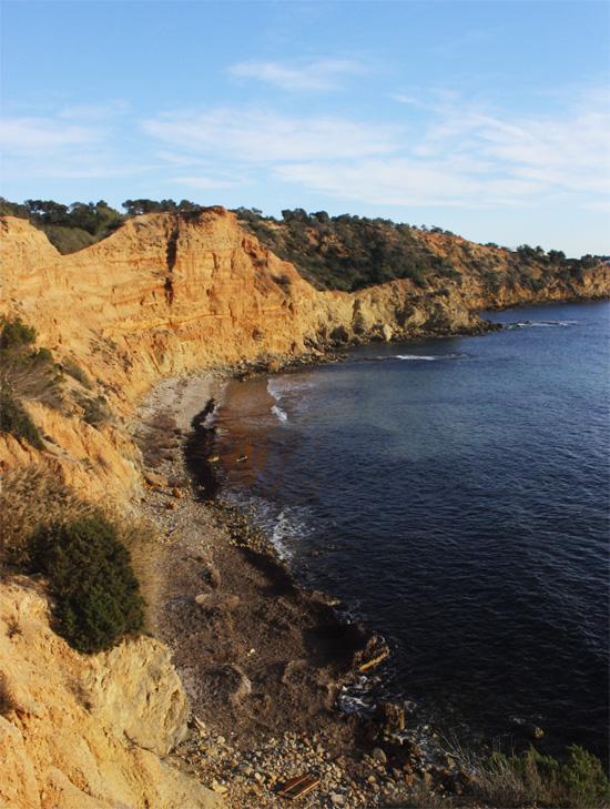 Panorámica de la playa de Sa Caixota. Al atardecer, el acantilado se tiñe de colores rojizos.