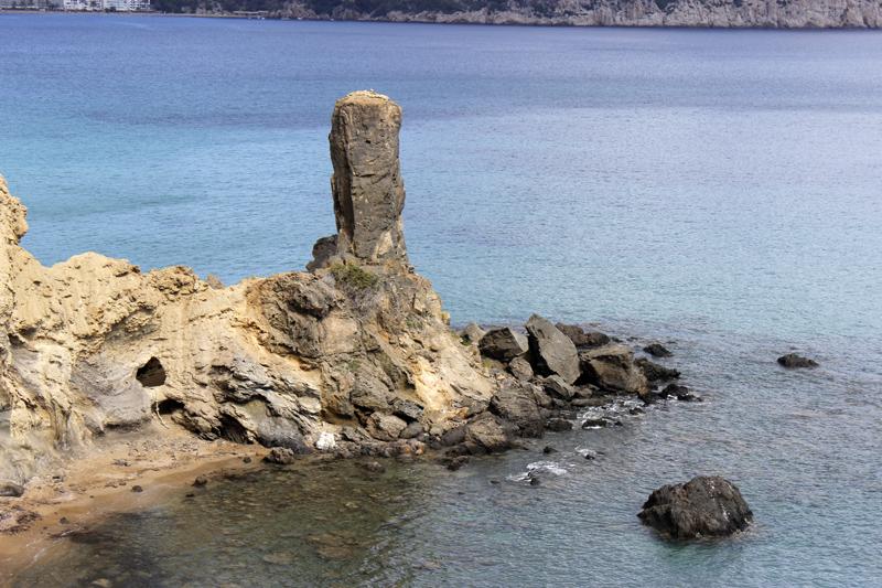 A la izquierda del monolito, se observa la cueva que da acceso a la playa de Es Racó de Ses Dones