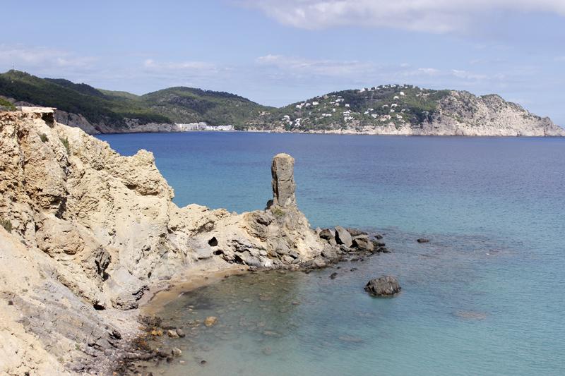 La playa de Es Racó des Paller d'en Camp, justo bajo el acantilado y el monolito.